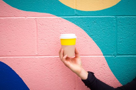 A girl holding a bright yellow coffee cup that is unbranded in front of a multi-color bright colored wall. The colors of your brand are just as important as your brand logo.
