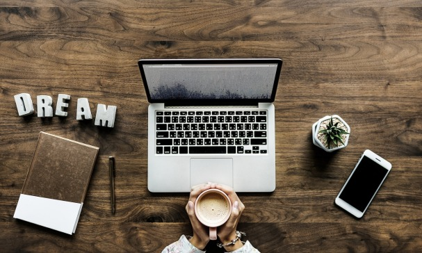 Small business owner holding a coffee surrounded by a journal, phone, computer and small plant and looking to hire a virtual assistant