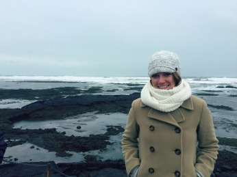 Tayler in Winter Hat, Scarf and Jacket Smiling in Front of Ocean in Iceland