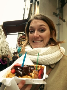 Tayler in the Street Holding a Belgium Waffle with Nutella and Strawberry Topping